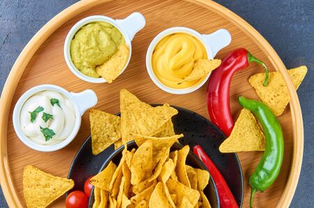 Nachos - yellow corn chips with various sauces in bowls: guacamole, cheese sauce, white sauce, on a dark background. Mexican food concept. The view from the top.