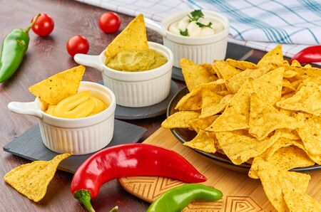 Nachos - yellow corn chips with various sauces in bowls: guacamole, cheese sauce, white sauce, on a wooden table. Mexican food concept. Stock Photo