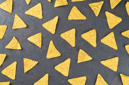 Nachos-yellow corn chips on a dark background. The concept of Mexican food. The view from the top.