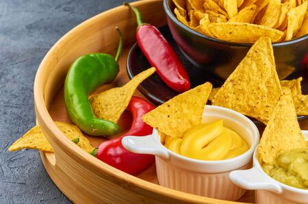 Nachos - yellow corn chips with various sauces in bowls: guacamole, cheese sauce, white sauce, on dark background. Mexican food concept.