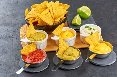 Nachos - yellow corn chips with various sauces in bowls: guacamole, cheese sauce, salsa sauce, white sauce, on dark background. Mexican food concept.