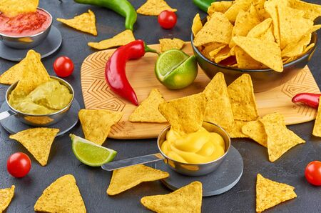Nachos - yellow corn chips with various sauces in bowls: guacamole, cheese sauce, salsa sauce, on dark background. Mexican food concept.