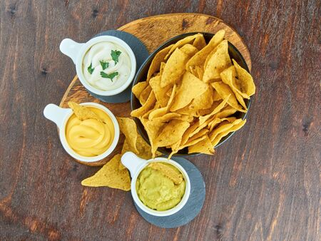 Nachos - yellow corn chips with various sauces in bowls: guacamole, cheese sauce, white sauce, on a wooden table. Mexican food concept. The view from the top. Stock Photo