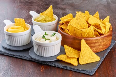 Nachos - yellow corn chips with various sauces in bowls: guacamole, cheese sauce, white sauce, on a wooden table. Mexican food concept. Stok Fotoğraf
