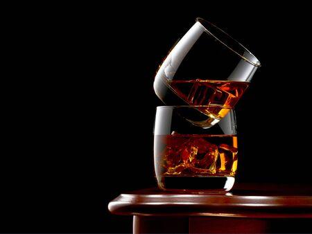 Dwie szklanki whisky i lodu na drewnianym stole. Szklanki są ułożone jeden na drugim. Niski klucz.