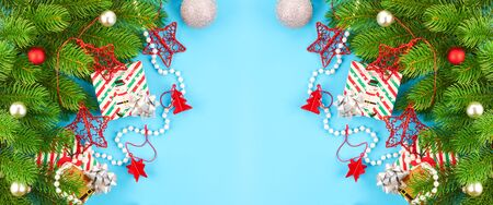 Christmas background with fir branches, various christmas decorations, colored garlands and beads, on a blue background. Christmas decoration. Christmas background. Space for text. Archivio Fotografico - 134095551