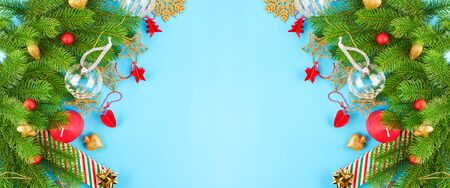 Christmas background with fir branches, various christmas decorations, colored garlands and beads, on a blue background. Christmas decoration. Christmas background. Space for text. Archivio Fotografico - 134095555