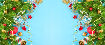 Christmas background with fir branches, various christmas decorations, colored garlands and beads, on a blue background. Christmas decoration. Christmas background. Space for text. Archivio Fotografico - 134095556