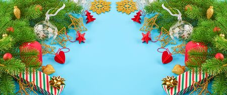 Christmas background with fir branches, various christmas decorations, colored garlands and beads, on a blue background. Christmas decoration. Christmas background. Space for text. Archivio Fotografico - 134424810
