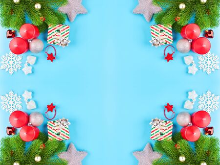 Christmas background with fir branches, various christmas decorations, colored garlands and beads, on a blue background. Christmas decoration. Christmas background. Space for text. Archivio Fotografico - 134285527