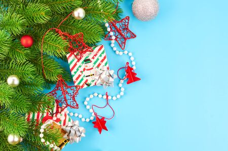 Christmas background with fir branches, various christmas decorations, colored garlands and beads, on a blue background. Christmas decoration. Christmas background. Space for text. Archivio Fotografico - 133807680