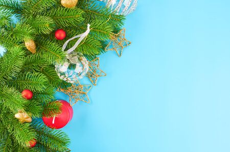 Christmas background with fir branches, various christmas decorations, colored garlands and beads, on a blue background. Christmas decoration. Christmas background. Space for text. Archivio Fotografico - 134279915