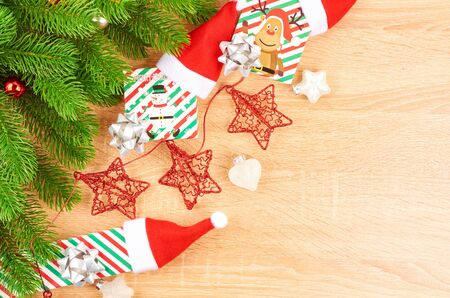 Christmas background with fir branches, various Christmas decorations, colored garlands and beads, on a light wood background. Christmas decorations. Christmas background. Space for text. Archivio Fotografico - 134279917
