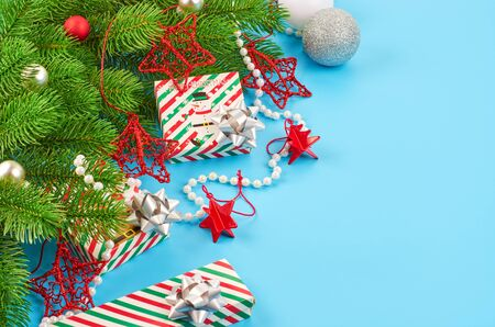 Christmas background with fir branches, various christmas decorations, colored garlands and beads, on a blue background. Christmas decoration. Christmas background. Space for text. Archivio Fotografico - 133936383