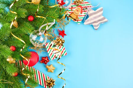 Christmas background with fir branches, various christmas decorations, colored garlands and beads, on a blue background. Christmas decoration. Christmas background. Space for text. Archivio Fotografico - 133936386