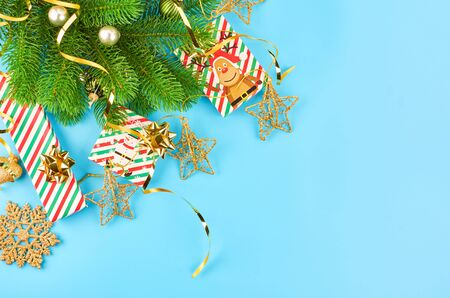Christmas background with fir branches, various christmas decorations, colored garlands and beads, on a blue background. Christmas decoration. Christmas background. Space for text. Archivio Fotografico - 133936387