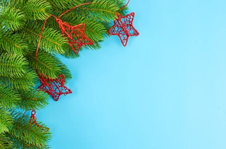 Christmas background with fir branches, various christmas decorations, colored garlands and beads, on a blue background. Christmas decoration. Christmas background. Space for text. Archivio Fotografico - 133936390