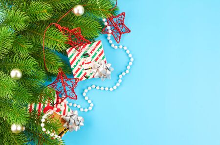Christmas background with fir branches, various christmas decorations, colored garlands and beads, on a blue background. Christmas decoration. Christmas background. Space for text. Archivio Fotografico - 133936393