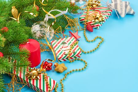 Christmas background with fir branches, various christmas decorations, colored garlands and beads, on a blue background. Christmas decoration. Christmas background. Space for text. Archivio Fotografico - 133936447