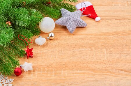 Christmas background with fir branches, various Christmas decorations, colored garlands and beads, on a light wood background. Christmas decorations. Christmas background. Space for text. Archivio Fotografico - 133936452