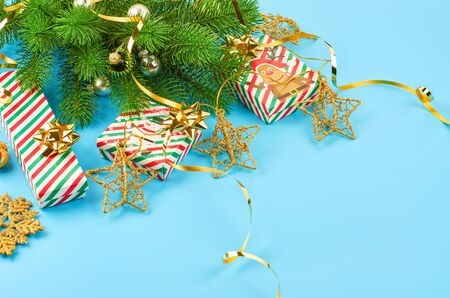 Christmas background with fir branches, various christmas decorations, colored garlands and beads, on a blue background. Christmas decoration. Christmas background. Space for text. Archivio Fotografico - 133936458