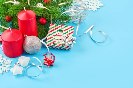 Christmas background with fir branches, various christmas decorations, colored garlands and beads, on a blue background. Christmas decoration. Christmas background. Space for text. Archivio Fotografico - 134279918