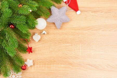 Christmas background with fir branches, various Christmas decorations, colored garlands and beads, on a light wood background. Christmas decorations. Christmas background. Space for text. Archivio Fotografico - 133937377