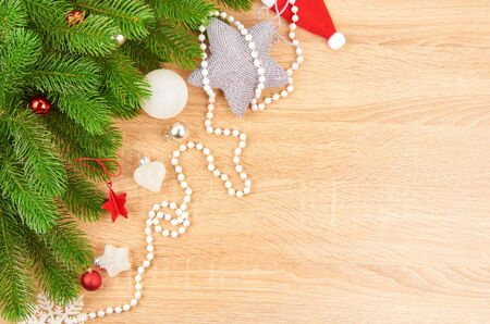 Christmas background with fir branches, various Christmas decorations, colored garlands and beads, on a light wood background. Christmas decorations. Christmas background. Space for text. Archivio Fotografico - 133937378