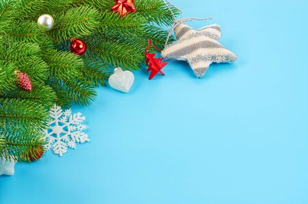 Christmas background with fir branches, various christmas decorations, colored garlands and beads, on a blue background. Christmas decoration. Christmas background. Space for text. Archivio Fotografico - 133884909