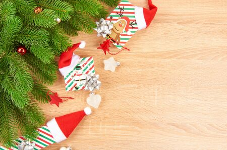 Christmas background with fir branches, various Christmas decorations, colored garlands and beads, on a light wood background. Christmas decorations. Christmas background. Space for text. Archivio Fotografico - 133884911