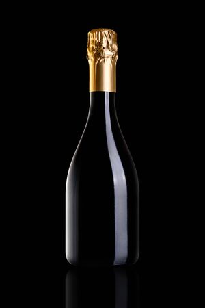 A bottle of champagne, isolated on a black background. The bottle is closed with gold foil. Archivio Fotografico - 134237479