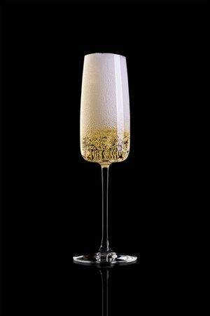 A glass of champagne isolated on a black background. In a wine glass high foam. Archivio Fotografico - 134237482