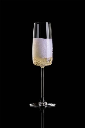 A glass of champagne isolated on a black background. The glass is half full. Archivio Fotografico - 134237480
