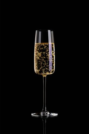 A glass of champagne isolated on a black background. Champagne in a glass without foam. Archivio Fotografico - 134237487