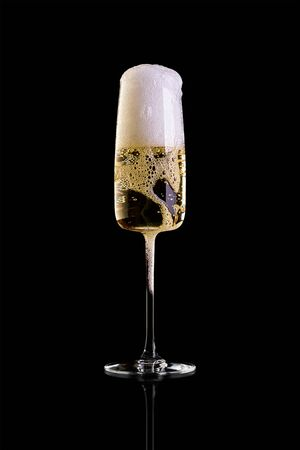A glass of champagne isolated on a black background. High foam pours out of the glass. Archivio Fotografico - 134237486