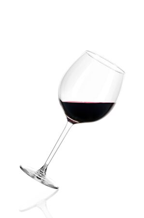 A glass of red wine half filled, isolated on a white background. The glass is tilted to the right. Archivio Fotografico - 135584697