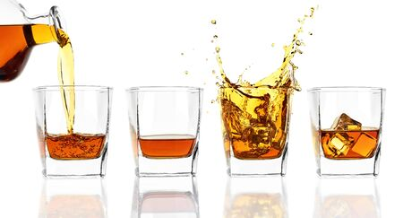 Four glasses of whiskey isolated on white background. Whiskey poured from a bottle, whiskey with ice, whiskey splashes. Archivio Fotografico - 135587346