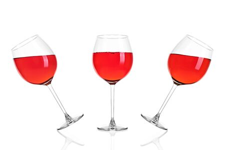 Three full glasses of rose wine half filled isolated on white background. Archivio Fotografico - 135587413