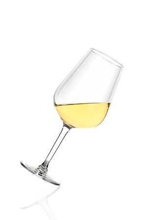 Glass of white wine half filled, isolated on white background. The glass is tilted to the right. Archivio Fotografico - 136036297