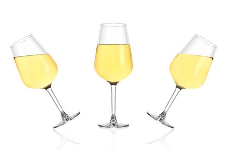 Three glasses of white wine isolated on white background. Glasses tilted in different directions, poured completely. Archivio Fotografico - 136036328