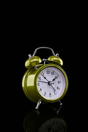 Yellow alarm clock with reflection on glass close-up isolated on dark background. Archivio Fotografico - 137446333