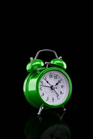 Green alarm clock with reflection on glass close-up isolated on dark background. Archivio Fotografico - 137446358