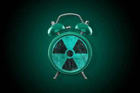 Gray-green alarm clock close-up on a dark background with a gray-green gradient. Radiation sign instead of clock face. Archivio Fotografico - 137446921