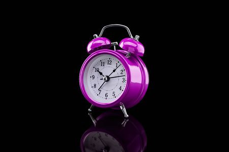 Purple alarm clock with reflection on glass close-up isolated on dark background. Archivio Fotografico - 137447657