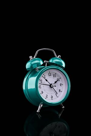 Turquoise alarm clock with reflection on glass close-up isolated on dark background. Archivio Fotografico - 137448334