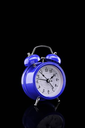 Blue alarm clock with reflection on glass close-up isolated on dark background. Archivio Fotografico - 137448255