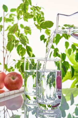 Two glasses of water on a green natural background. The glass is filled with water from a bottle