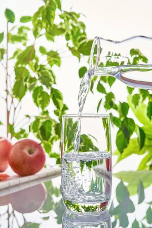 Glass of water on a green natural background. The glass is filled with water from a bottle Imagens