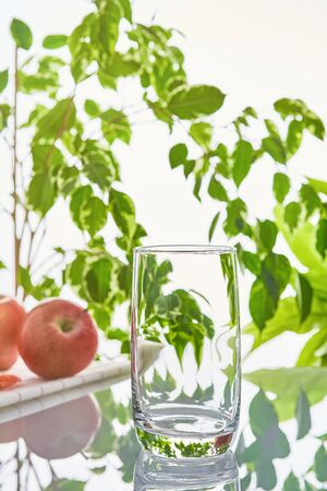 Water glass on a background of green leaves. Imagens