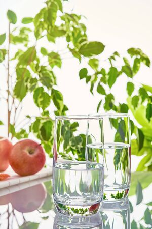 Two glasses of water on a background of green leaves in the sunlight. Imagens